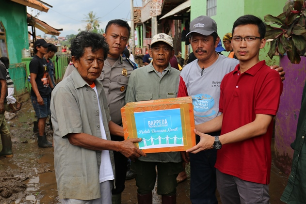 Kepala Sub Bagian Umum Bappeda Provinsi Jawa Barat Anjar Yusdinar, S.STP., M.Si menyerahkan bantuan kepada warga di Kampung Cimacan, Desa Haurpanggung, Kecamatan Tarogong Kidul, Jumat (23/9/16).