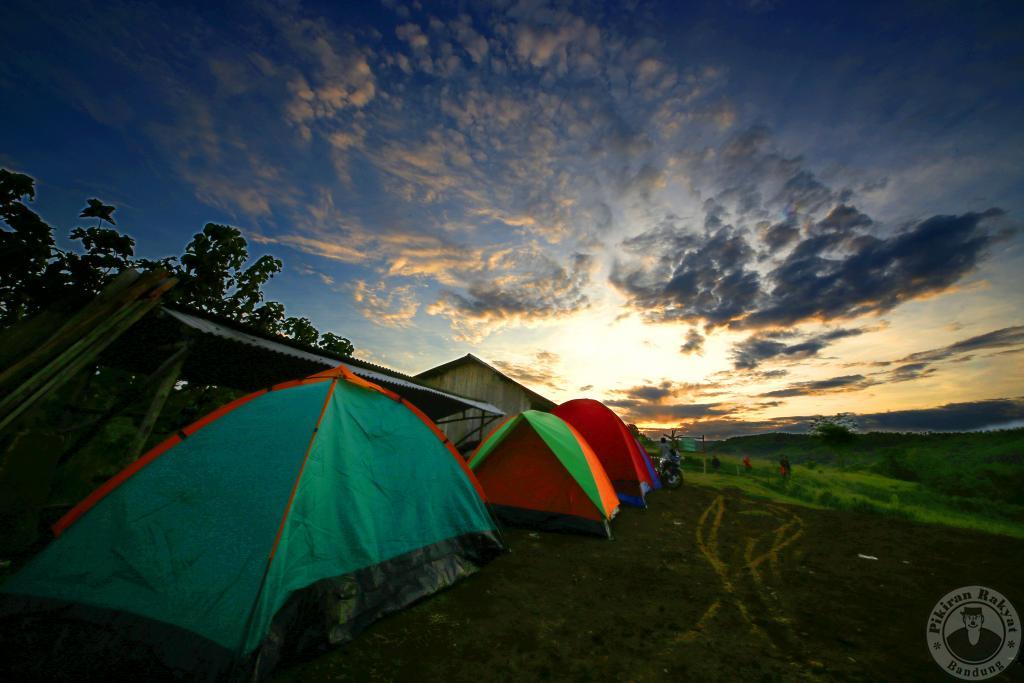 Matahari pagi mengintip dari balik bukit di Puncak Darma